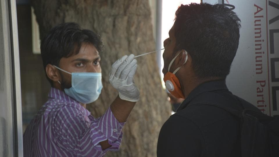 A health worker collects a swab sample from a man for coronavirus testing, at MMG Hospital, in Ghaziabad (Photo by Sakib Ali /Hindustan Times)