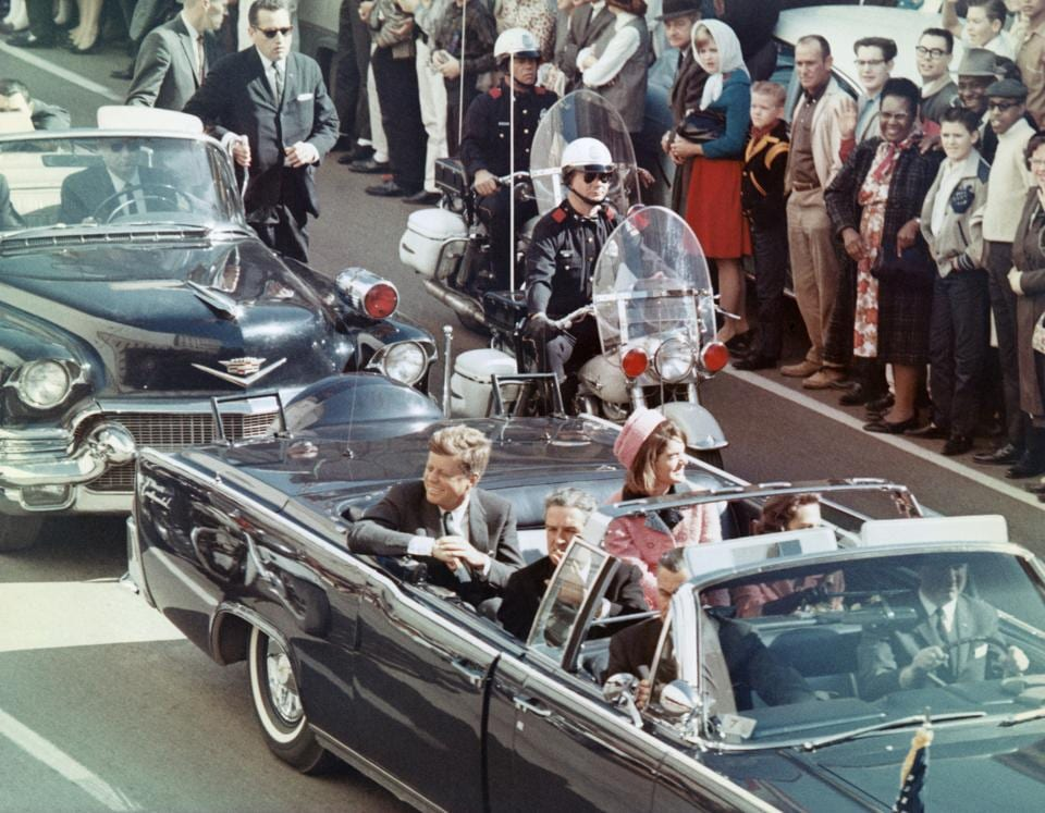 President and Mrs John F Kennedy smile at the crowds lining their motorcade route in Dallas, Texas, on November 22, 1963. Minutes later the President was assassinated as his car passed through Dealey Plaza.