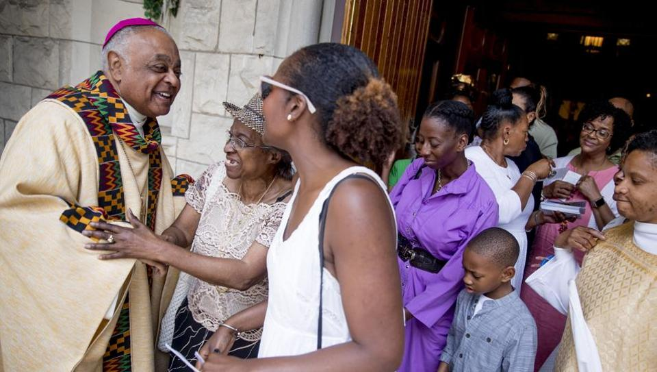 In this photo, Washington DC Archbishop Wilton Gregory greets parishioners following Mass at St. Augustine Church in Washington.