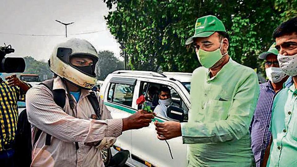 Environment minister Gopal Rai offers a flower to a commuter at Rajpath as part of the campaign.