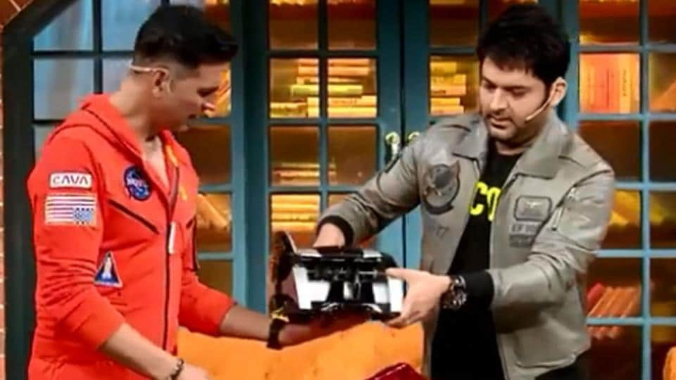 Akshay Kumar with his gift, a money counting machine, on The Kapil Sharma Show.