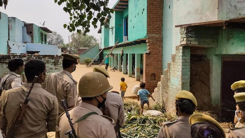Police personnel stand guard as CBI officials investigate the case of a 19-year-old Dalit woman who died after being allegedly gang-raped inHathras.