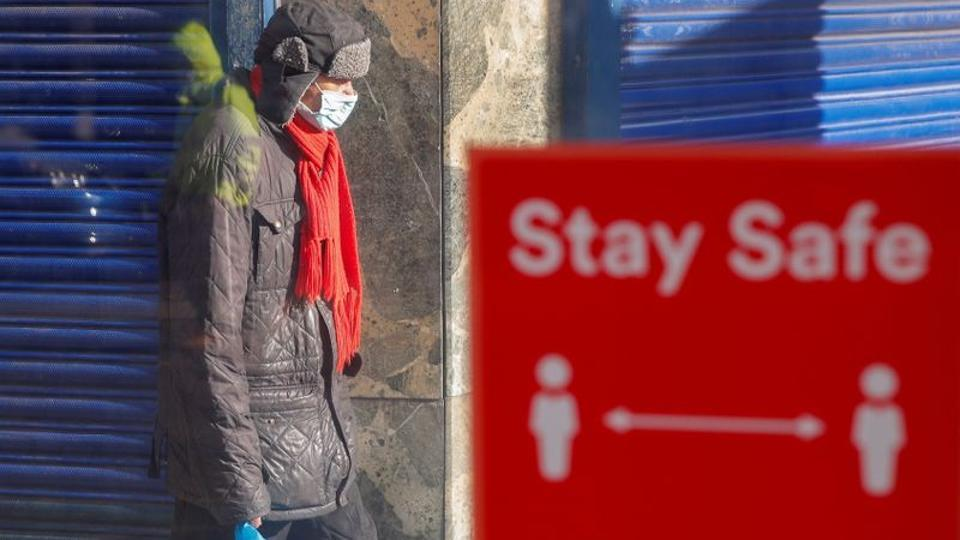 FILE PHOTO: A person wearing a protective mask walks near a social distancing sign, amid the outbreak of the coronavirus disease (COVID-19), in Coventry, Britain October 25, 2020.