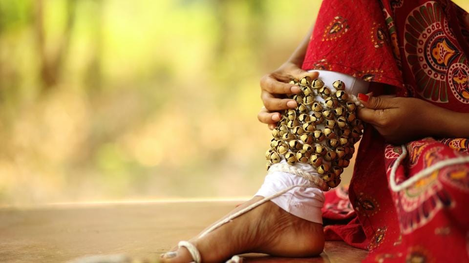 Close up of a young female kathak dancer tying ghungroo to her legs.