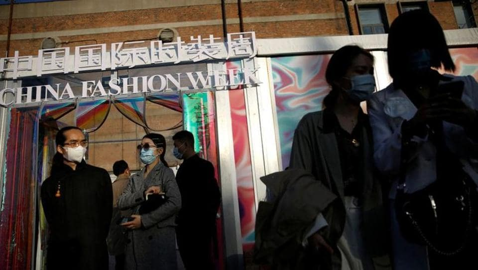 People wearing protective masks, following the coronavirus disease (COVID-19) outbreak, are seen outside a venue of China Fashion Week in Beijing, China October 24, 2020.