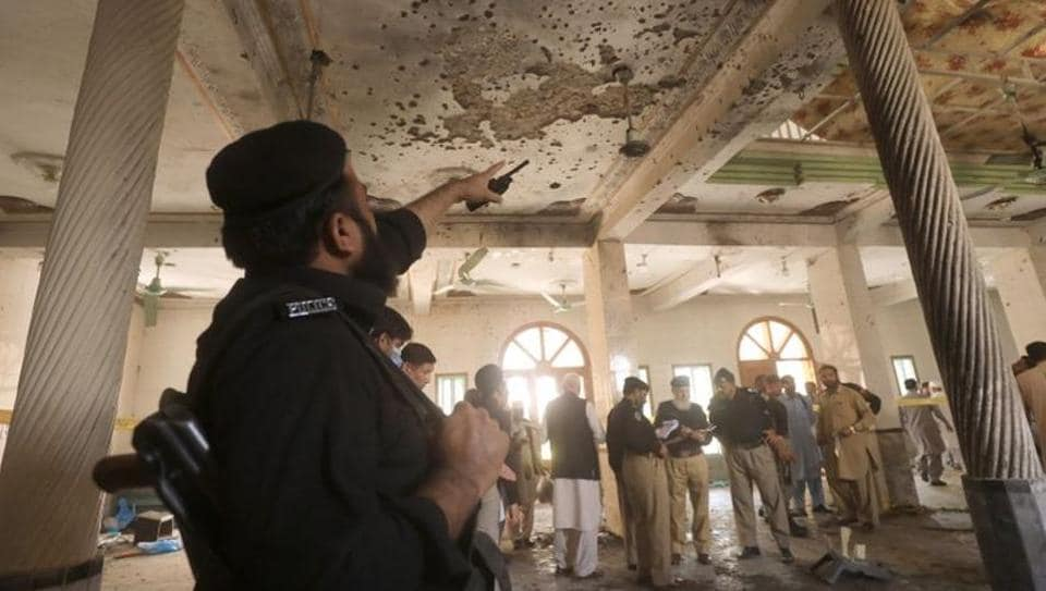 A police officer points to the damaged roof while others survey the site of a bomb blast at a religious seminary in Peshawar, Pakistan on October 27.