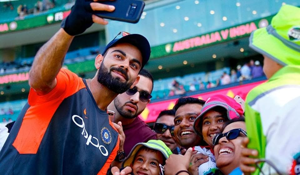 Indian captain Virat Kohli takes a selfie with the crowd.