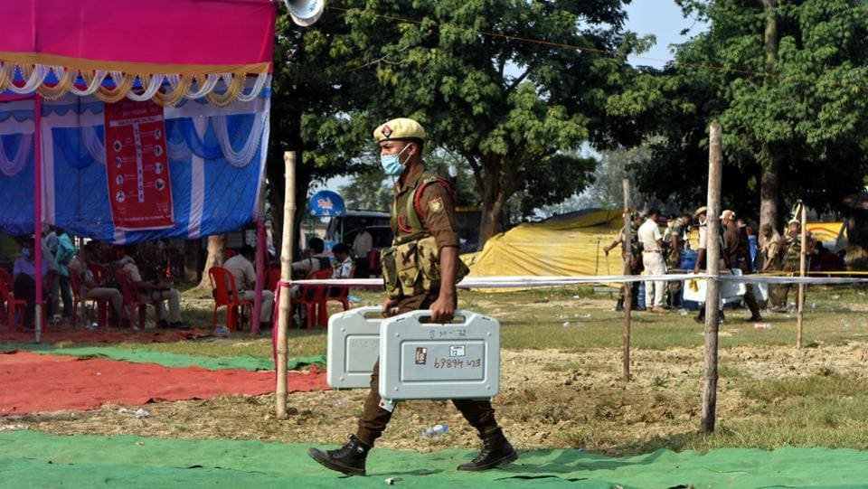 A security personnel carries Electronic Voting Machines (EVM) on the eve of Bihar Assembly elections, at Bharatpura near Patna on October 27. People from 71 assembly constituencies across 16 districts voted today during the first phase of Bihar Assembly elections. (Parwaz Khan / HTPhoto)