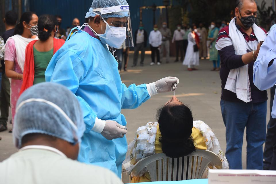A health worker collects a swab sample from a woman for coronavirus testing at a government office, at Minto Road in New Delhi (Photo by Raj K Raj/ Hindustan Times)