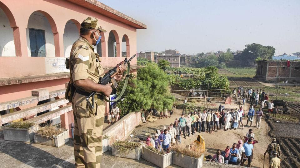 A security official keeps a vigil as voters stand in queues at a polling station to cast their votes for the first phase of Bihar Assembly Election, at Masaurhi in Patna, Wednesday.