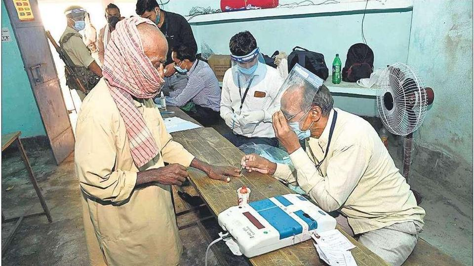 An election officer wears a face shield as a protective measure against Covid at a polling station in Paliganj on Wednesday.