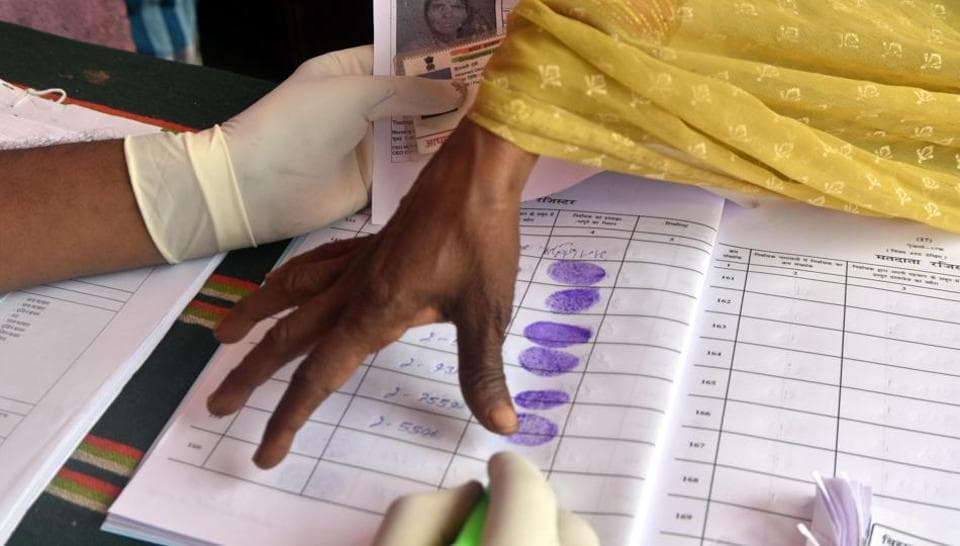An election officer notes voter's detail during the first phase of Bihar Assembly elections, at Bikram constituency, in Patna on Wednesday, Oct 28, 2020. (Photo by Parwaz Khan / Hindustan Times)