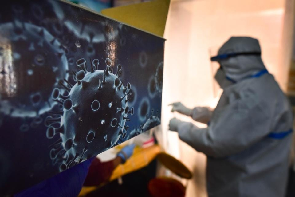 An illustration of the novel coronavirus seen next to a health care worker at a Covid-19 testing centre in New Delhi on October 28. India's Covid-19 tally crossed eight million cases on October 29, after the country logged almost 50,000 new infections over the last 24 hours, taking its tally to 8,040,203, according to the Union Health Ministry's daily bulletin. (Sanchit Khanna / HT Photo)