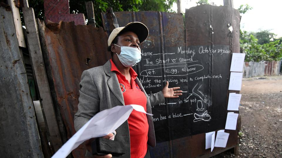 Educator Taneka Mckoy Phipps teaches a lesson next to a blackboard painted on a zinc fence.