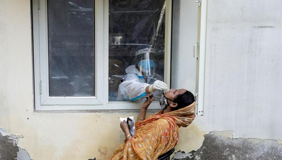 FILE PHOTO: A health worker in personal protective equipment (PPE) collects a sample using a swab from a person at a local health centre to conduct tests for the coronavirus disease (COVID-19), amid the spread of the disease, in New Delhi, India October 7, 2020.