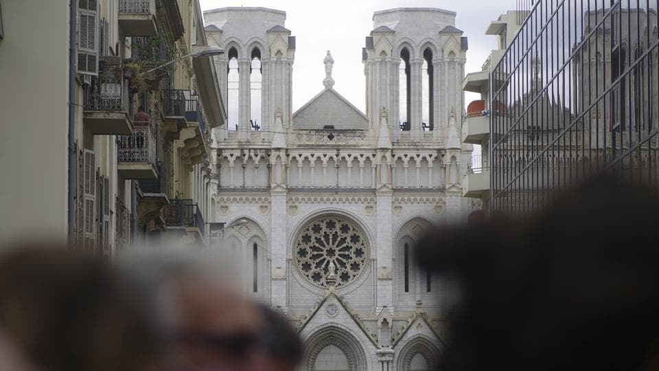 People and journalist stand near the scene of the knife attack at the Notre Dame church, in Nice, France, Thursday, Oct. 29, 2020. An attacker armed with a knife killed three people at a church in the Mediterranean city of Nice, the third attack in two months in France.