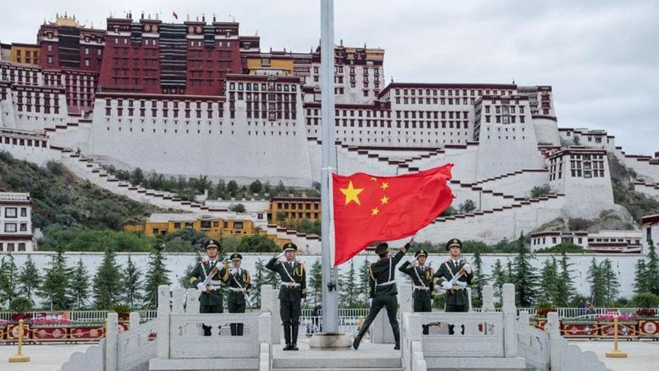 A file photo of the Chinese national flag being raised during a ceremony  in Lhasa.