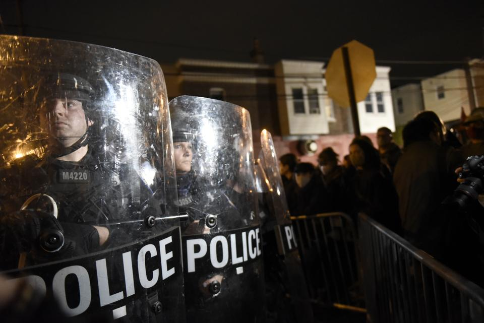 Philadelphia police officers form a line during a demonstration in Philadelphia, late Tuesday, Oct. 27, 2020. Hundreds of demonstrators marched in West Philadelphia over the death of Walter Wallace Jr., a Black man who was killed by police in Philadelphia on Monday. (AP Photo/Michael Perez)