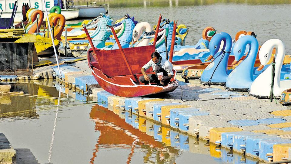 A worker painting a boat at Sukhna Lake in Chandigarh on Friday.