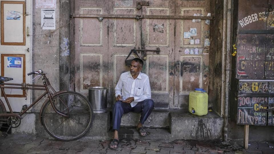 A man sits outside a closed store in Mumbai.