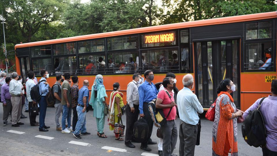 Commuters queue to board DTC buses at Pandit Pant Marg near Central Secretariat in New Delhi.