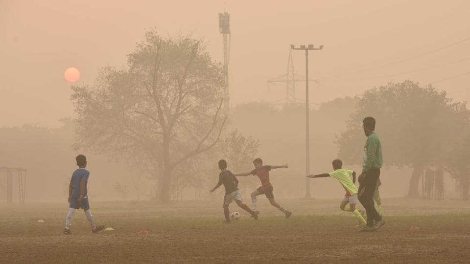 Children playing football on a hazy morning in New Delhi.