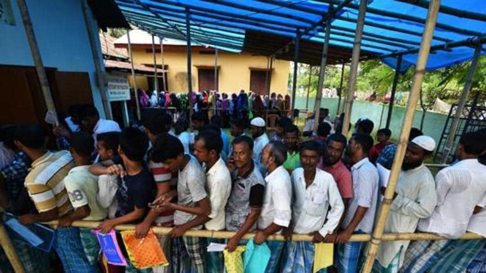 People wait in queue to check their names on the draft list at the NRC centre at an Assam village.