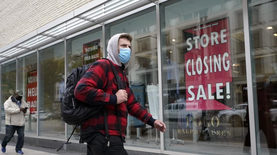 A passer-by walks past a store closing sign, right, in the window of a department store on Oct. 27, 2020, in Boston.