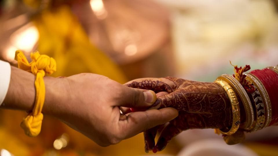 A bride and groom holding hands during wedding ceremony in this representative image.