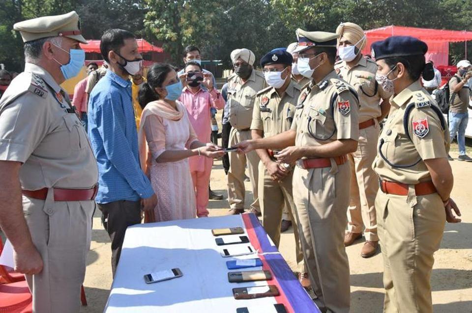 Police commissioner Rakesh Agrawal handing over people's belongings on supardari in Ludhiana on Friday.