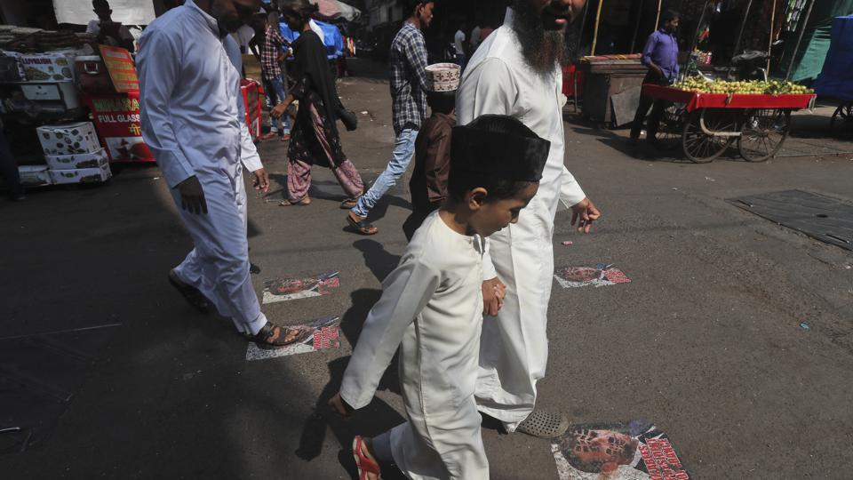 Protesters walk on defaced images of French President Emmanuel Macron pasted on a street in Mumbai, India.