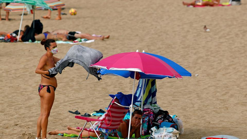 FILE PHOTO: A woman wearing a protective mask is seen on the beach in Las Palmas, Canary Islands, Spain, August 13, 2020.