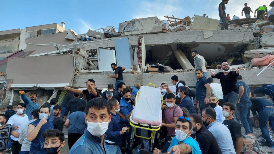 Locals and officials search for survivors at a collapsed building after a strong earthquake struck the Aegean Sea on Friday and was felt in both Greece and Turkey, where some buildings collapsed in the coastal province of Izmir, Turkey, October 30, 2020.