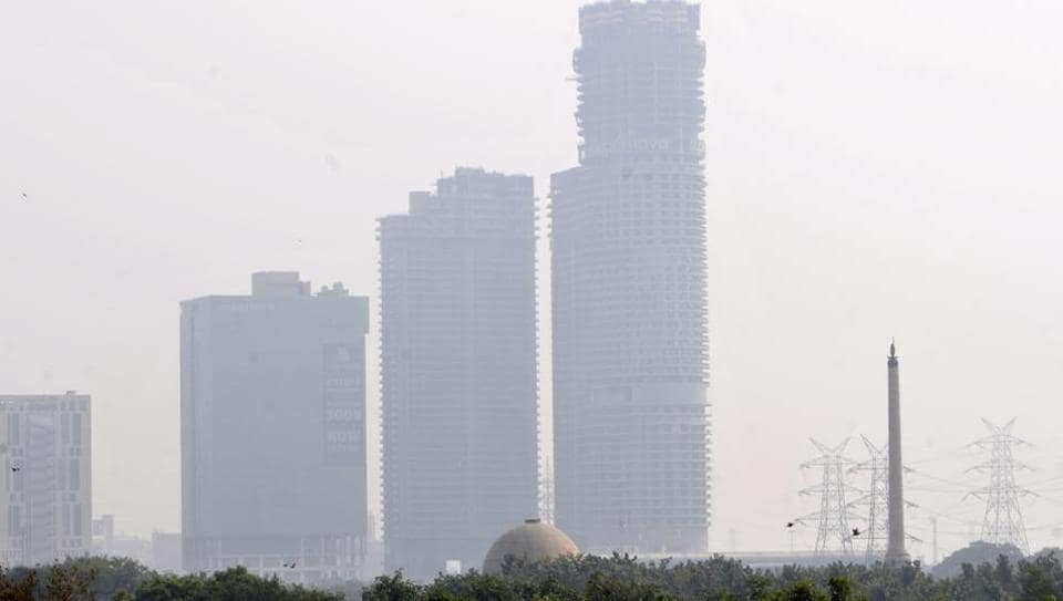 A view of skyscrapers blanketed in haze amid rising air pollution, at Sector 96, in Noida. (Photo by Sunil Ghosh / Hindustan Times)