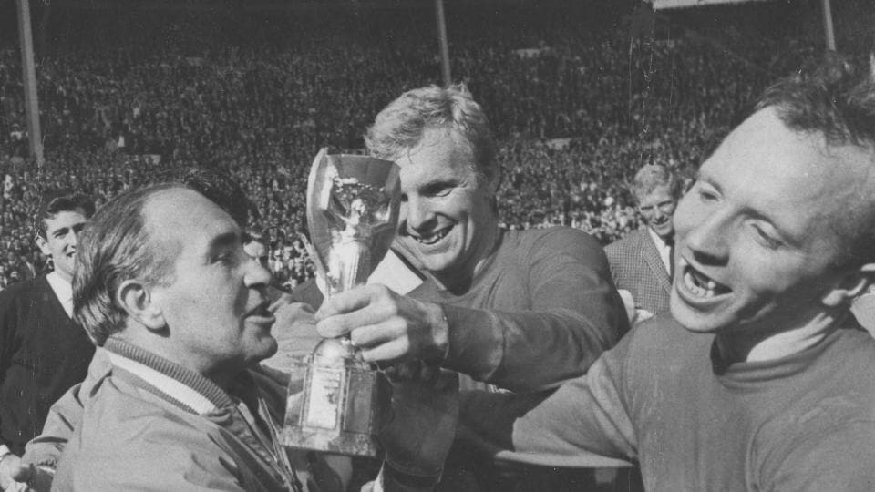 FILE - In this July 30, 1966 file photo, England midfield player Nobby Stiles, right, looks at the Jules Rimet Cup, held by England captain Bobby Moore after they had won the World Cup Final at Wembley, London.