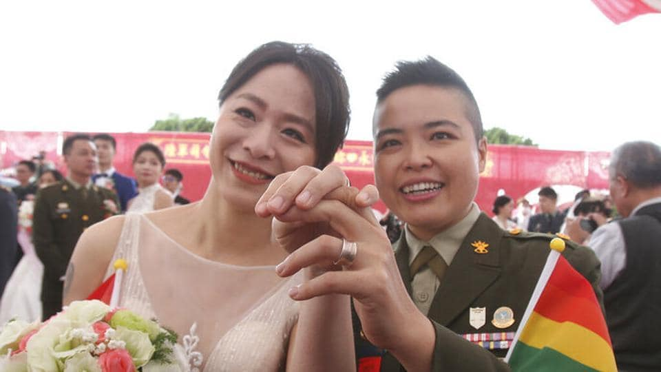 Lesbian couple Yi Wang, right, and Yumi Meng show their wedding rings during a military mass weddings ceremony in Taoyuan city, northern Taiwan.