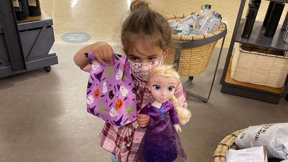 The image shows the little girl with her Elsa doll.