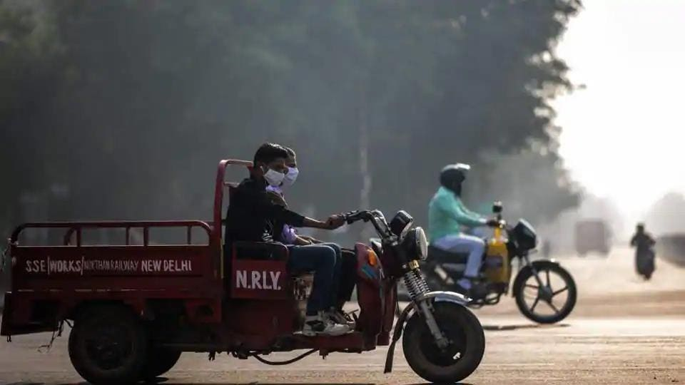 People wearing face masks ride along a street amid smoggy conditions in New Delhi on October 30.