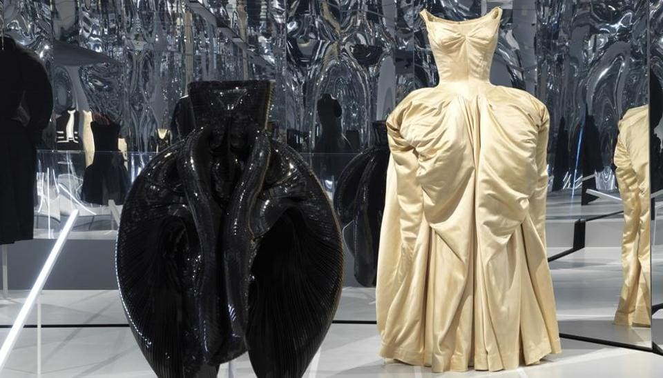 This image released by the Metropolitan Museum of Art in New York shows a black dress by Dutch designer Iris Van Herpen, left, and a ball gown by American designer Charles James, part of The Costume Institute's exhibition