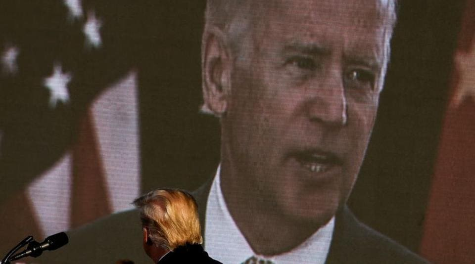 Democratic US presidential nominee and former Vice President Joe Biden is seen on a screen as US President Donald Trump watches a campaign add during his campaign rally at Green Bay Austin Straubel International Airport in Green Bay, Wisconsin.