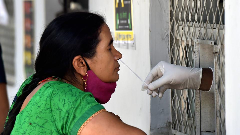 A health worker collects a sample from a woman for COVID-19 test, at a dispensary in New Delhi on Saturday.