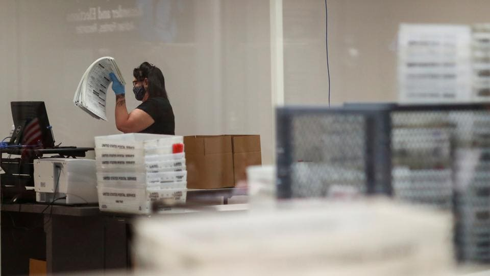 A woman works at the Maricopa County Elections ballot processing center in Phoenix, Arizona US on October 30, 2020.