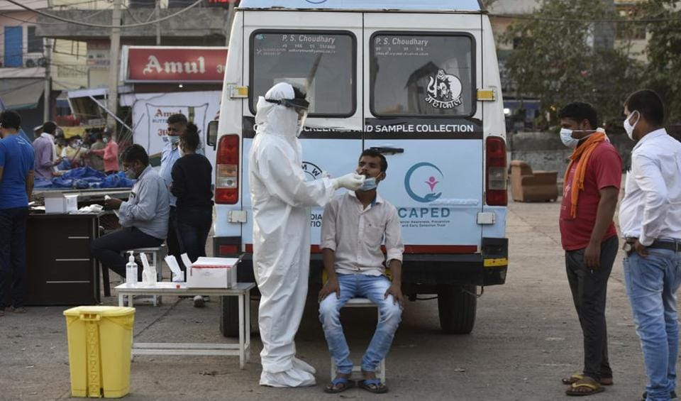 A health worker collects a swab sample for coronavirus test at Khandsa road, in Gurugram.