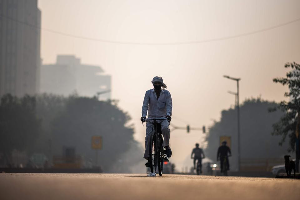 A man wearing a facemask rides his bicycle along a street amid smoggy condition in New Delhi on October 30.