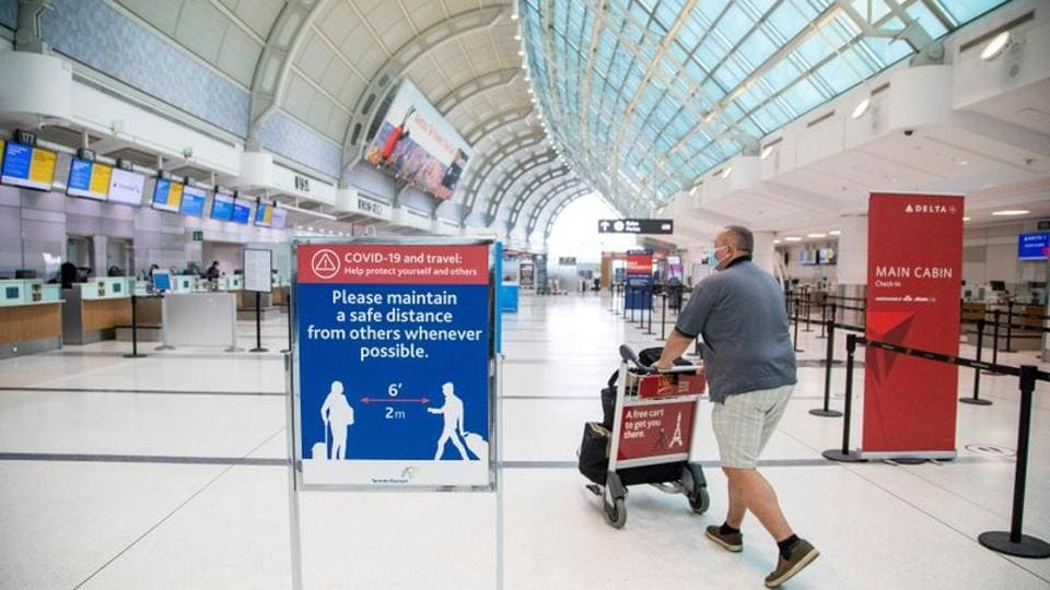 FILE PHOTO: A man pushes a baggage cart wearing a mandatory face mask as a