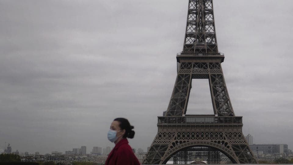 A woman walks near the Eiffel Tower in Paris, on the first day of a new month-long nationwide lockdown across France, on October 30. From midnight, France's 65 million people were largely confined to their homes, needing written statements to leave, in the latest drastic measure to curb a disease that has infected more than 45 million people worldwide and killed nearly 1.2 million. (Thibault Camus / AP)