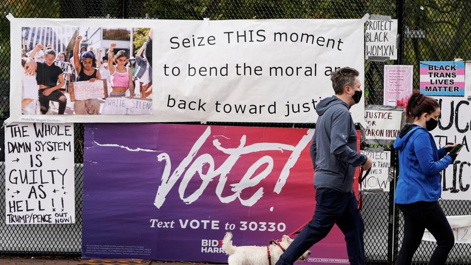 Pedestrians walks past a vote sign on a security fence ahead of Election Day near the White House in Washington, DC, US on October 31, 2020.