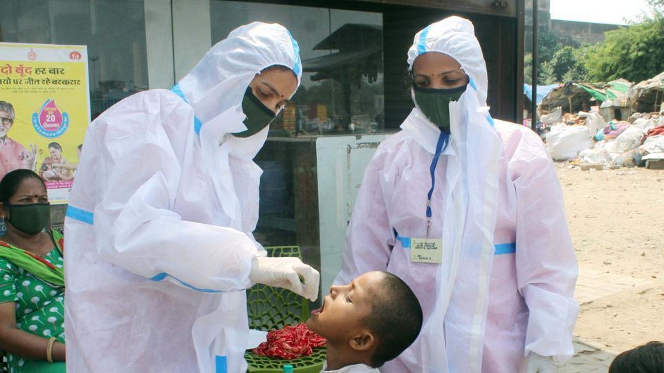 A child being administered pulse polio vaccine drops by an ANM worker.