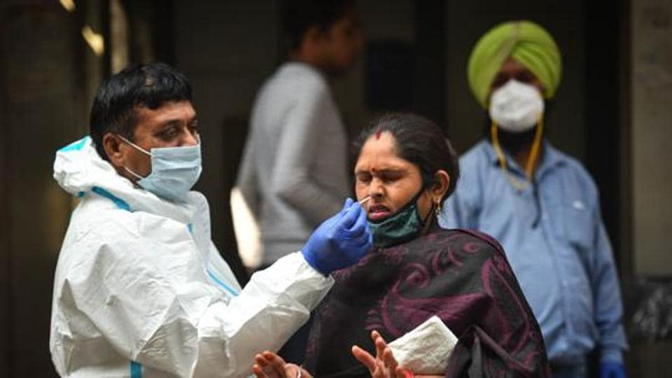 A health worker in PPE coveralls collects a swab sample from a woman for coronavirus testing, in Jahangirpuri, New Delhi.