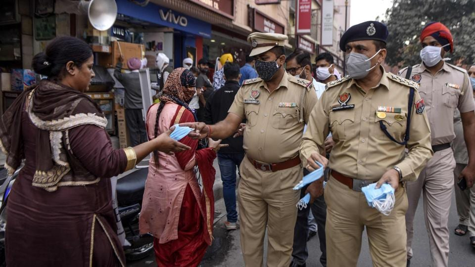 Police personnel distribute face masks to people on the streets in Amritsar on November 12. India has reported less than 50,000 new coronavirus disease (Covid-19) cases for eight days in a row as on November 16, as the total number of cases in the country approaches nine million, according to data released by the Union Ministry of Health and Family Welfare. (Narinder Nanu / AFP)